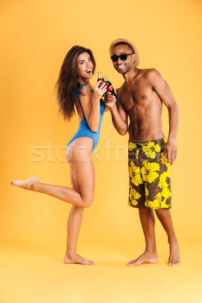 Young smiling multiracial couple clinking bottles Stock photo © deandrobot
