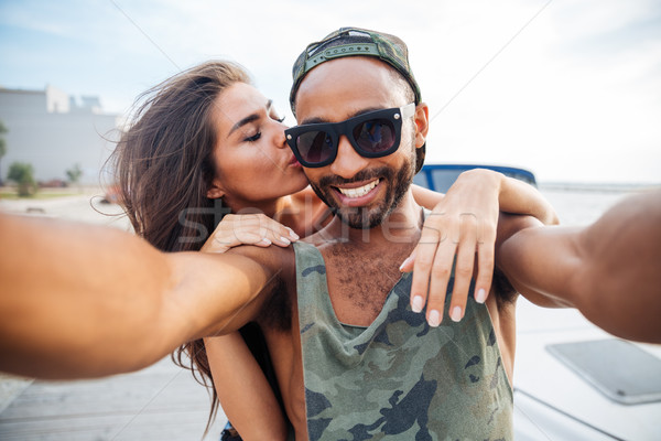 Smiling man and woman making selfie photo on smartphone Stock photo © deandrobot