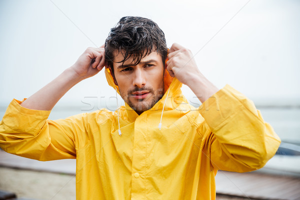 Portrait of a sailor man in yellow cloak Stock photo © deandrobot