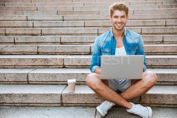 Man student using laptop while sitting on the staircase outdoors Stock photo © deandrobot