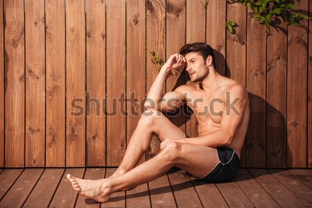 Pensive man sitting at the poolside and looking away Stock photo © deandrobot