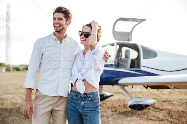 Couple standing in front of small private airplane Stock photo © deandrobot