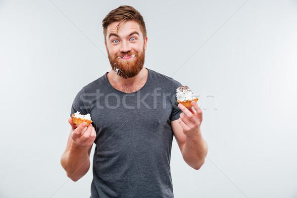 Happy smiling bearded man eating cream cake Stock photo © deandrobot