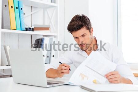 Zijaanzicht geconcentreerde jonge zakenman naar documenten Stockfoto © deandrobot