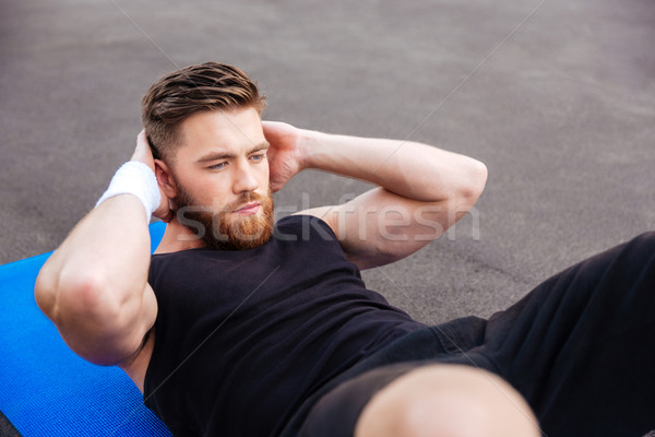 Concentrated handsome sports man doing press workout outdoors Stock photo © deandrobot