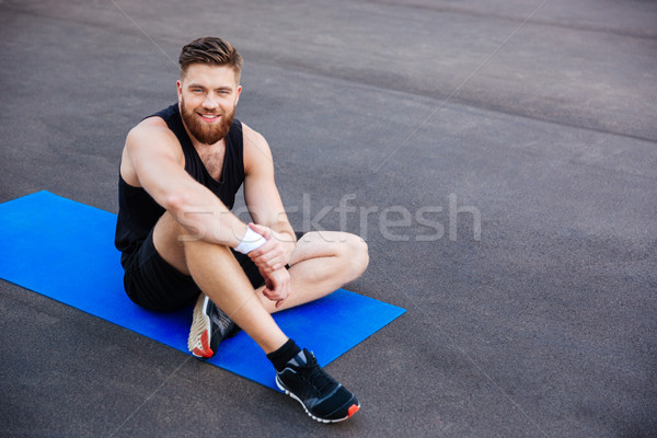 Sports man sitting and resting on blue fitness mat outdoors Stock photo © deandrobot