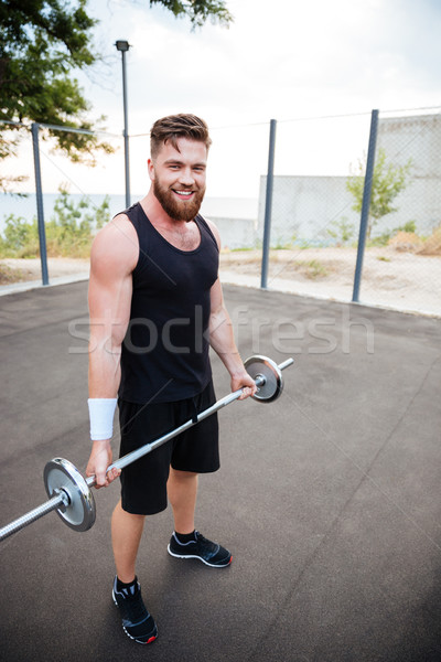 Attractive smiling sportsman standing and holding barbell Stock photo © deandrobot