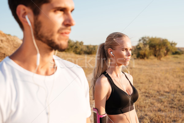 Young fitness couple standing together with earphones and looking away Stock photo © deandrobot
