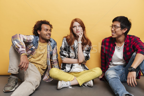 Thoughful young woman sitting and thinking between two smiling men Stock photo © deandrobot