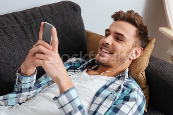 Lachend man sofa luisteren Stockfoto © deandrobot