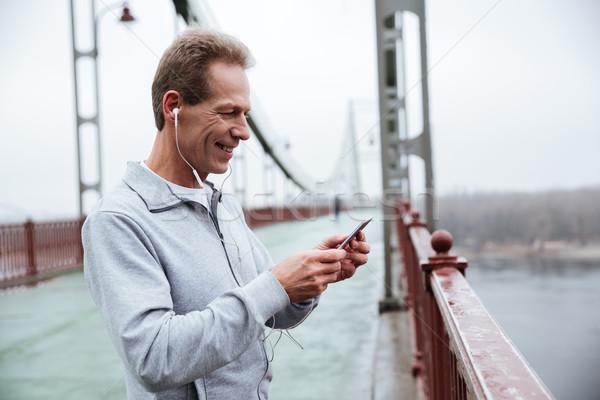 Side view of Runner listening to music on bridge Stock photo © deandrobot