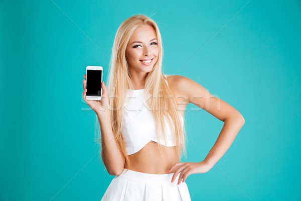 Smiling pretty woman standing and holding blank screen mobile phone Stock photo © deandrobot
