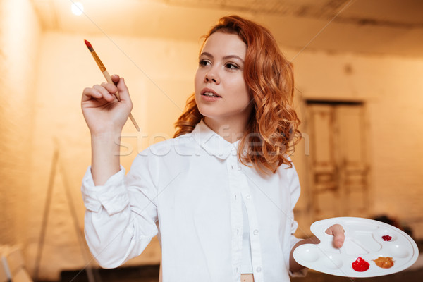 Concentrated redhead young woman painting with oil paints and palette Stock photo © deandrobot