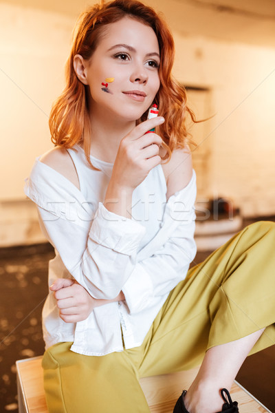 Concentrated young lady painter holding oil paints. Stock photo © deandrobot