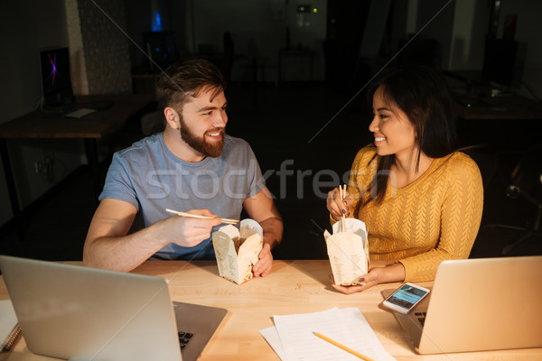 Business colleagues working at night while eating. Stock photo © deandrobot