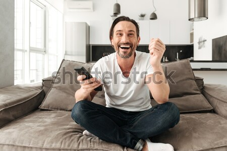 Surprised asian man watching tv on sofa Stock photo © deandrobot