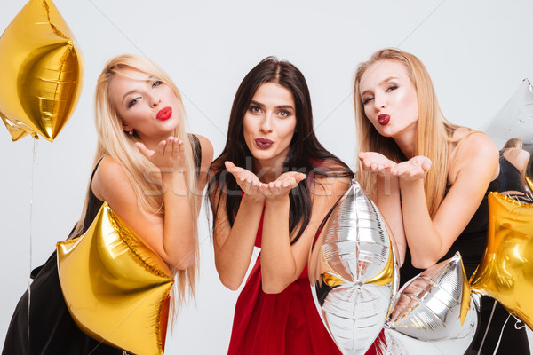Three happy playful women with star shaped balloons sending kisses Stock photo © deandrobot