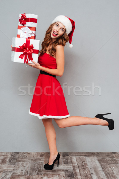 Girl with christmas gifts in full growth Stock photo © deandrobot