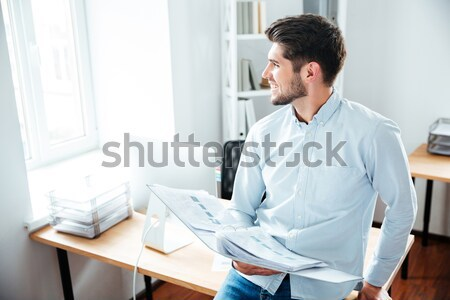 Tired young businessman with painful feelings holding his back. Stock photo © deandrobot