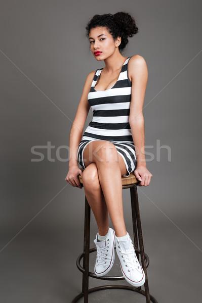 Mujer sesión silla mirando cámara Foto stock © deandrobot