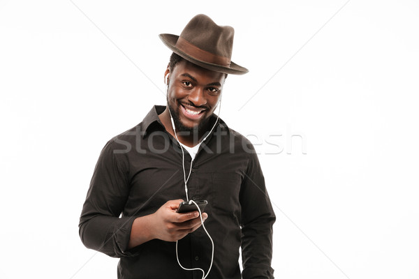 Stock photo: African man chatting by phone and listening music.