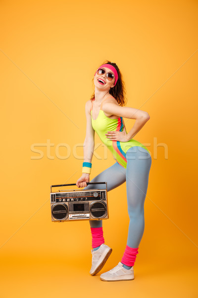 Attractive young sportswoman standing and posing with retro boombox Stock photo © deandrobot