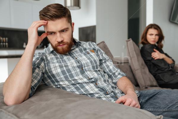 Quarrel loving couple sitting on sofa indoors. Stock photo © deandrobot