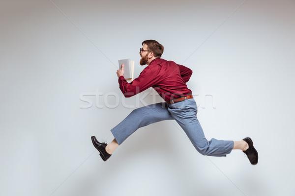 Masculino nerd corrida livros estúdio isolado Foto stock © deandrobot