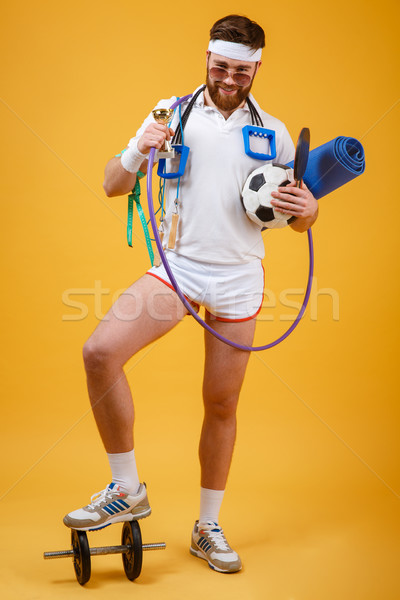 Happy satisfied man champion holding golden cup and sports equipment Stock photo © deandrobot