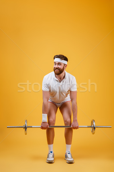 Full length of athletic man doing squatting exercises with barbell Stock photo © deandrobot