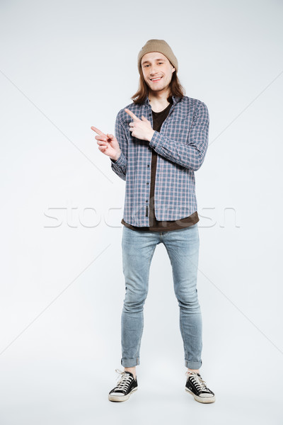 Vertical image of hipster pointing away Stock photo © deandrobot