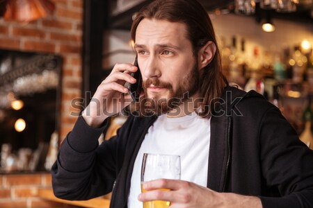 Bearded man talking on phone with cup of beer Stock photo © deandrobot