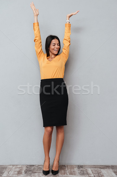 Full length portrait of a happy cheerful business woman celebrating success with hands raised Stock photo © deandrobot