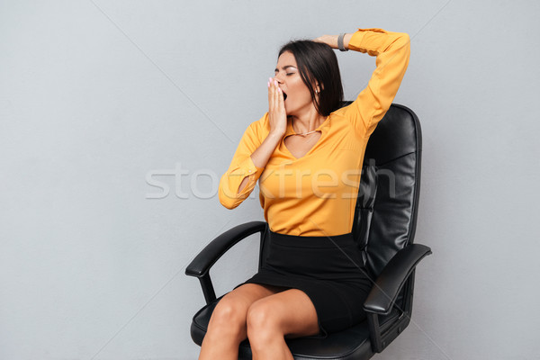 Tired exhausted business woman yawning while sitting on chair Stock photo © deandrobot
