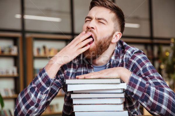 Young tired male student yawning while sitting at the library Stock photo © deandrobot
