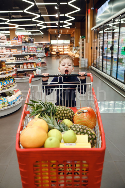 Vertical image of boy pushing shopping trolley Stock photo © deandrobot