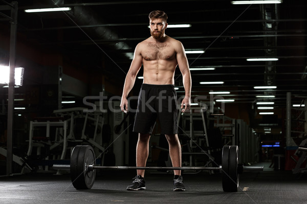 Stock photo: Concentrated sports man make sport exercises with barbell