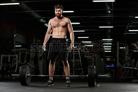 Strong sports man make sport exercises with barbell Stock photo © deandrobot