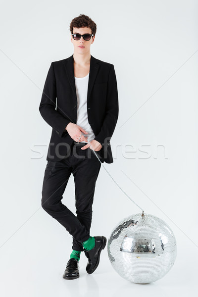 Vertical image of man in suit with disco ball Stock photo © deandrobot