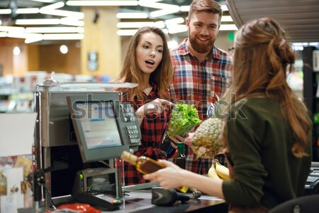 Stock photo: Cheerful cashier woman on workspace in supermarket