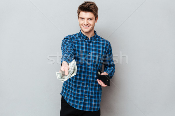 Young man giving cash to camera Stock photo © deandrobot