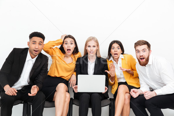 Shocked colleagues sitting in office using laptop computer. Stock photo © deandrobot