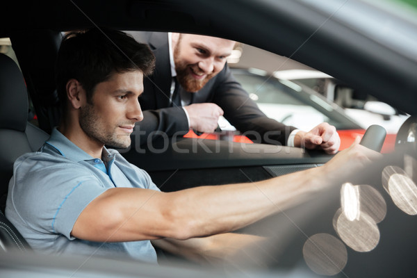 Young man testing a new car with a salesperson Stock photo © deandrobot