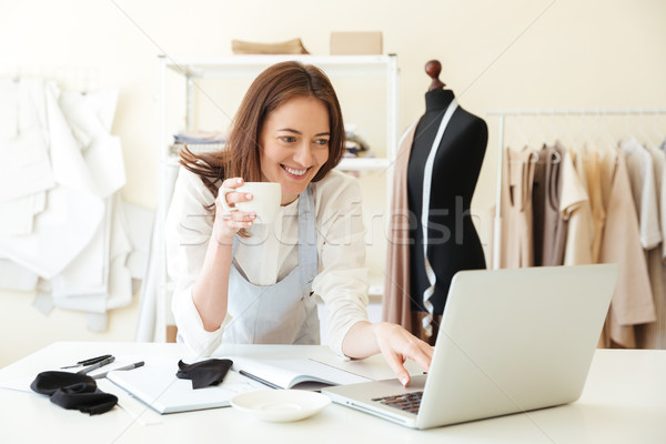 Seamstress in blue apron using laptop and drinking coffee Stock photo © deandrobot