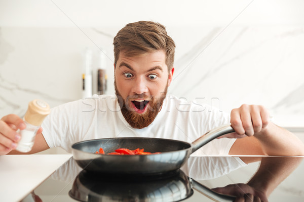 Happy shocked bearded man sprinkle with salt of vegetables Stock photo © deandrobot