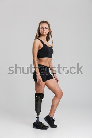 Smiling fitness woman sitting on the floor and tie shoelaces Stock photo © deandrobot