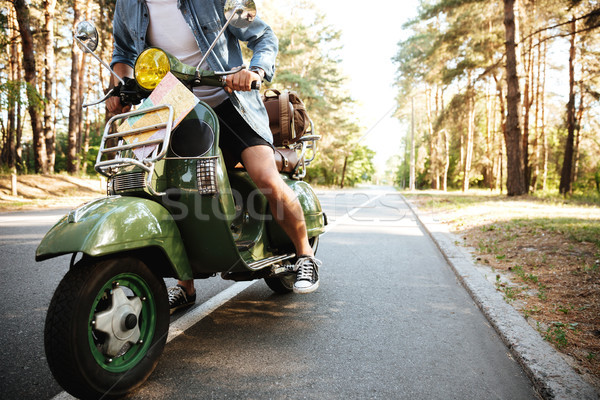 Young man on scooter outdoors. Stock photo © deandrobot