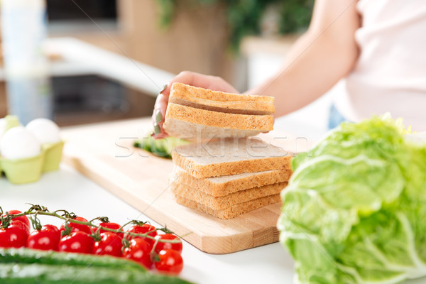 Woman making sandwiches with vegetables on a cutting board Stock photo © deandrobot