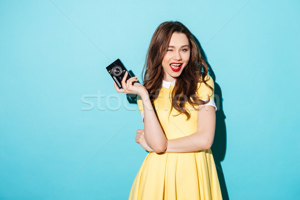 Playful young woman in dress holding retro camera and winking Stock photo © deandrobot