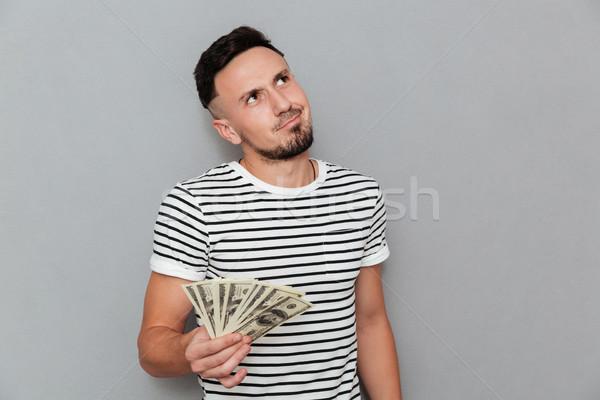 Töprengő férfi póló tart pénz felfelé néz Stock fotó © deandrobot
